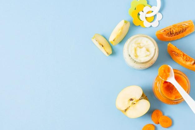 Alimentos para bebés sobre fondo azul plano lay