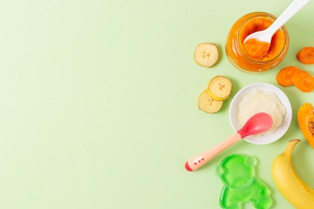 Alimentos para bebés sobre fondo verde encima de la vista