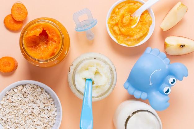 Alimentos para bebés en la vista superior de fondo rosa