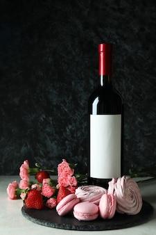 Alimentos dulces y botella de vino en blanco sobre fondo negro ahumado