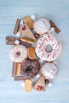 Alimentos dulces nocivos sobre fondo de madera azul