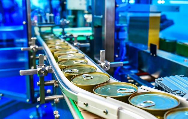Alimentos enlatados en cinta transportadora en almacén de distribución