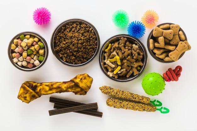 Alimentos para mascotas en cuencos y juguetes aislados sobre fondo blanco.