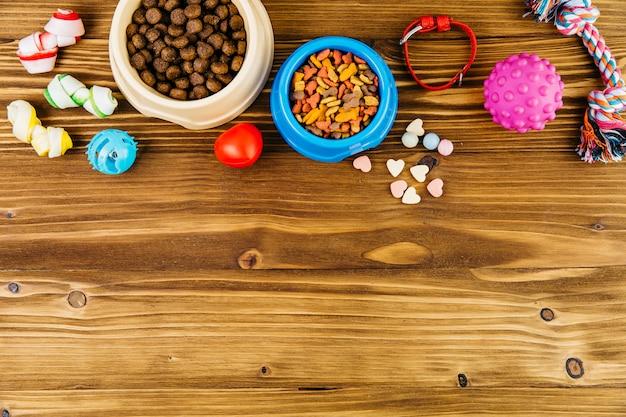 Alimentos para mascotas y juguetes en superficie de madera.