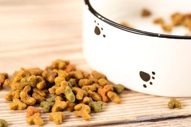 Alimentos para mascotas en un recipiente sobre una mesa de madera junto al recipiente blanco