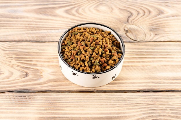 Alimentos para mascotas en un recipiente sobre una mesa de madera