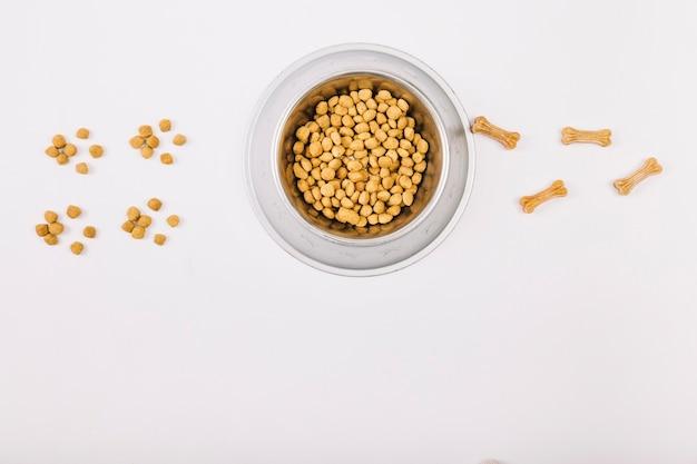 Alimentos y masticar huesos cerca del tazón