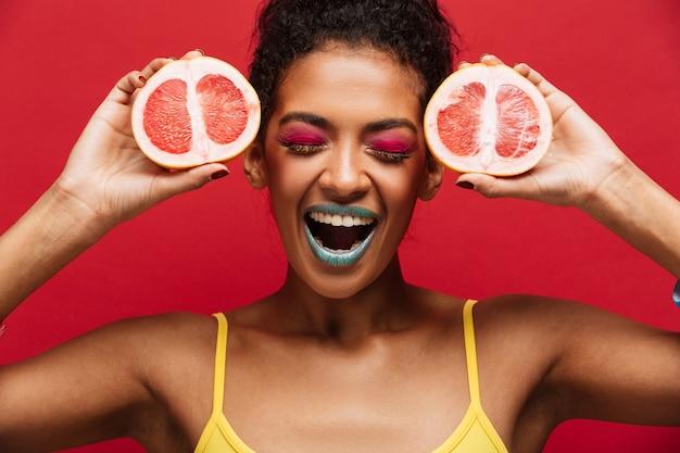 Alimentos moda encantada mujer afroamericana divirtiéndose sosteniendo dos mitades de pomelo maduro fresco en la cara, aislado sobre la pared roja