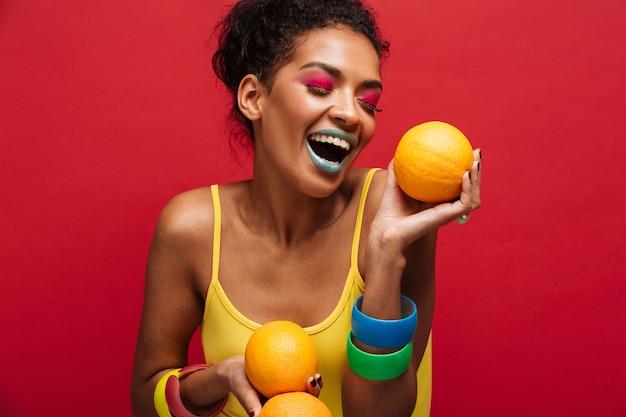 Alimentos moda mujer alegre de raza mixta con maquillaje colorido divirtiéndose con muchas naranjas maduras en las manos, aislado sobre la pared roja
