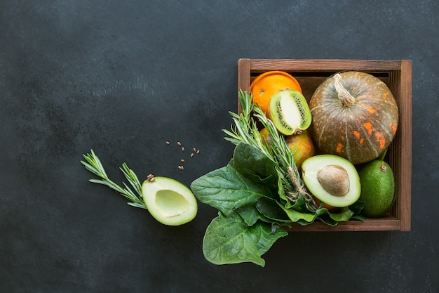 Alimentos orgánicos de agricultores saludables en caja de madera: frutas, verduras, semillas, superalimento, verdura de hoja sobre fondo negro. concepto de selección de alimentación limpia