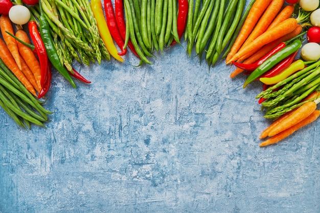 Alimentos orgánicos. capítulo de verduras coloridas en fondo azul brillante.