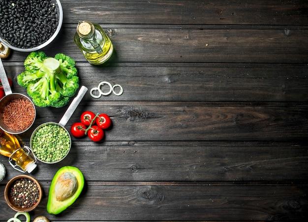Alimentos orgánicos. diferentes verduras crudas con champiñones y aceite de oliva en una mesa de madera.