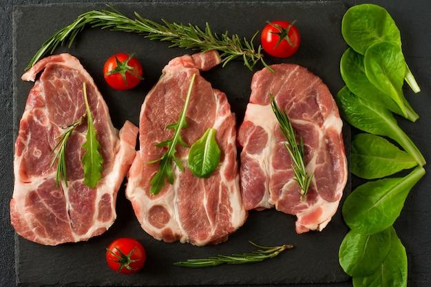 Alimentos orgánicos frescos cuello de cerdo crudo en piedra pizarra negra con romero, cebolla y tomates.