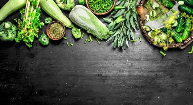 Alimentos orgánicos. pepinos frescos con hierbas en la pizarra negra.
