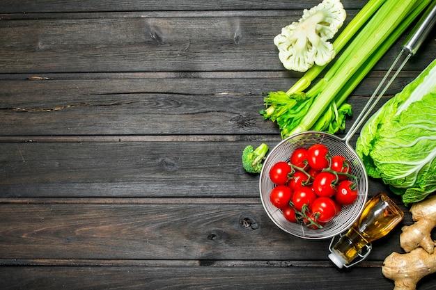 Alimentos orgánicos. tomates maduros con verduras en una mesa de madera.