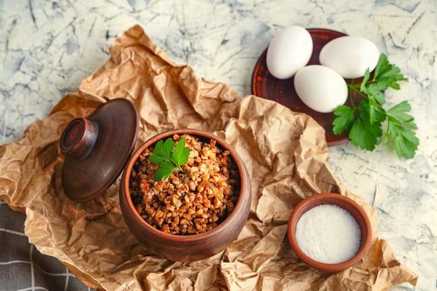 Alimentos ricos en proteínas, desayuno saludable, concepto de comida sana, dieta, papilla de trigo sarraceno, en una olla, huevos duros