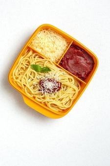 Alimentos saludables en envases de plástico listos para comer con espaguetis caseros con tomate, queso y albahaca sobre la mesa de trabajo. comida italiana. para llevar.