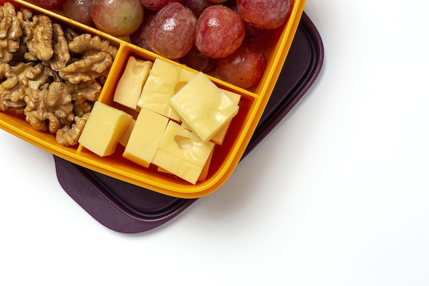 Alimentos saludables en envases de plástico listos para comer con queso, uvas y nueces en la mesa de trabajo. para llevar nueces. aislado