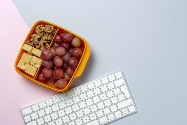 Alimentos saludables en envases de plástico listos para comer con queso, uvas y nueces en la mesa de trabajo. para llevar nueces
