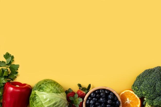 Alimentos saludables, frutas y verduras aisladas sobre fondo amarillo