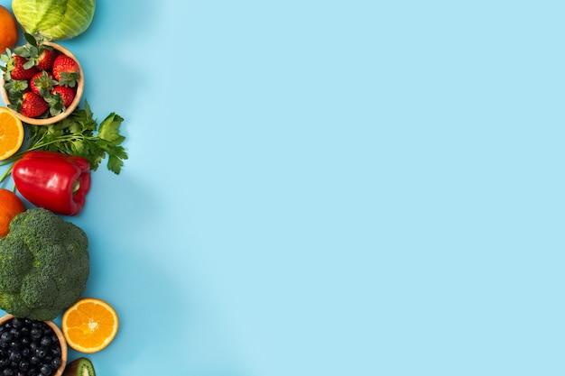 Alimentos saludables, frutas y verduras aisladas sobre fondo azul