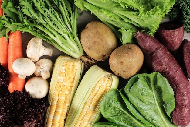 Alimentos saludables, varias verduras frescas hojas sobre un fondo de madera de mármol marrón. vista superior. copie el espacio. col rizada, lechuga, lechuga morada, escarola, zanahoria, champiñones, maíz, boniato morado, patata