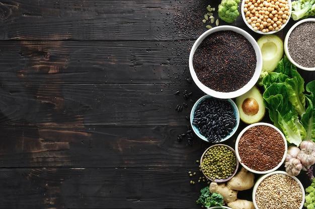 Alimentos sanos y limpios comiendo vegetales, semillas, superalimentos, cereales, hojas y verduras sobre un fondo oscuro copia espacio