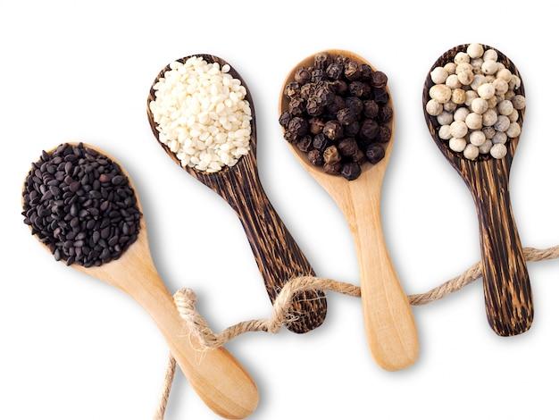 Alimentos secos hierbas saludables con sésamo y pimienta en la cuchara de madera con una cuerda aislada en la superficie blanca.