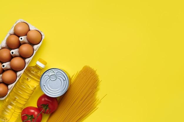 Alimentos sobre fondo amarillo, huevos de gallina, aceite de girasol, tomates, pasta, conservas, vista superior, flatlay