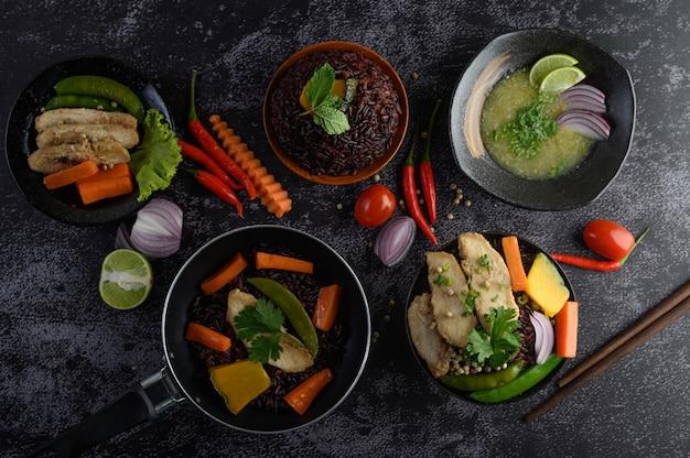 Alimentos variados y platos de verduras, carne y pescado en una mesa de piedra negra. vista superior.
