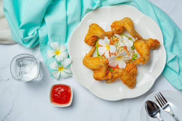 Alitas fritas con salsa de pescado, bellamente decoradas y servidas.