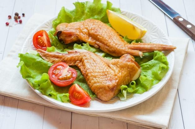 Alitas de pollo ahumadas con lechuga fresca tomate y limón. copia espacio