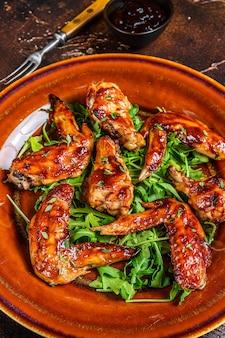 Alitas de pollo al horno con salsa de chile dulce en un plato con rúcula. vista superior.