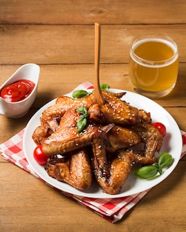 Alitas de pollo de alto ángulo en un plato con semillas de sésamo y salsa de tomate