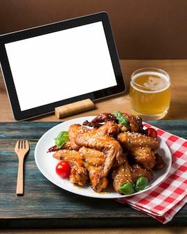 Alitas de pollo de alto ángulo en un plato con semillas de sésamo