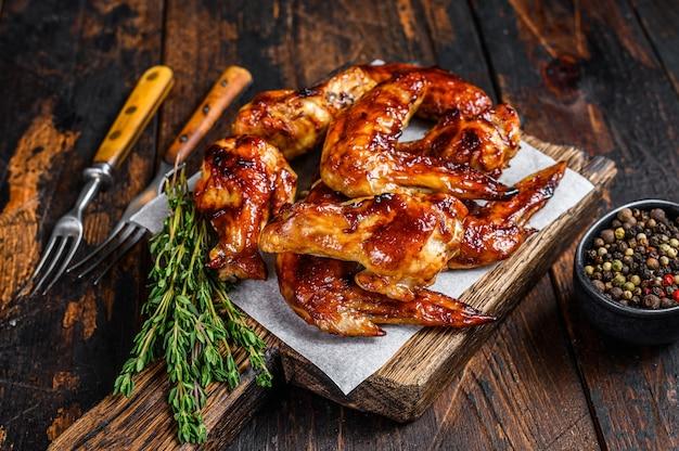 Alitas de pollo asadas al horno con salsa dip. mesa de madera oscura. vista superior.