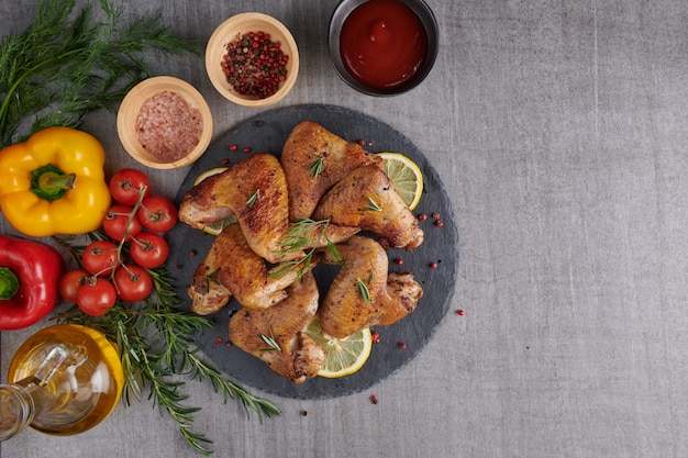 Alitas de pollo asadas en salsa barbacoa y ensalada mixta de verduras con pepitas de romero, sal en placa de piedra negra sobre mesa de piedra gris.