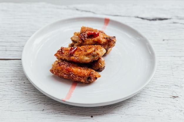 Las alitas de pollo coreanas se mezclan con una salsa estilo coreana servida en un plato blanco.