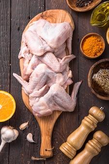 Alitas de pollo crudas con ingredientes para cocinar: miel, fruta de naranja, ajo, aceite de oliva, kari en una tabla de cortar de madera sobre una superficie de madera. vista superior .