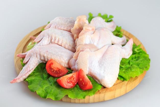 Alitas de pollo crudas sobre fondo blanco.