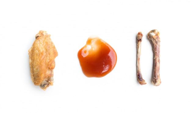 Alitas de pollo frito y hueso de pollo aislado