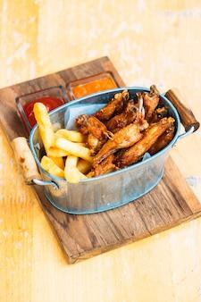 Alitas de pollo frito con papas fritas