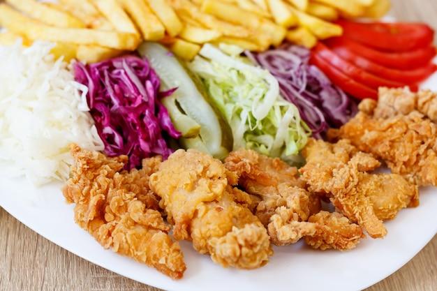 Alitas de pollo frito y verduras