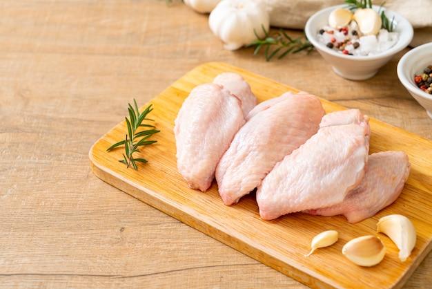 Alitas de pollo medio crudas frescas sobre tabla de madera