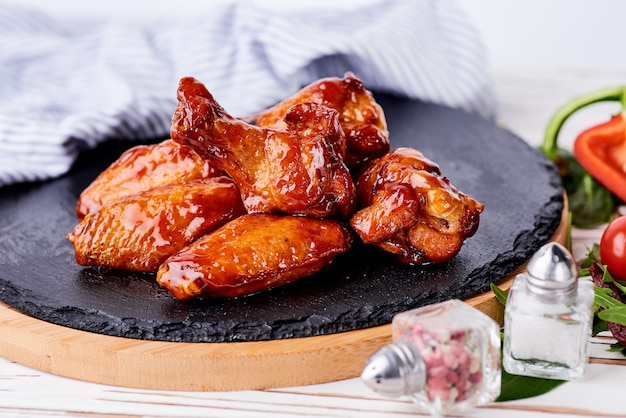 Alitas de pollo a la parrilla sobre fondo de piedra negra.