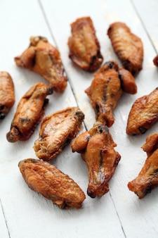 Alitas de pollo a la parrilla sobre una mesa blanca