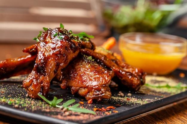 Alitas de pollo y patas indias al horno en salsa de mostaza y miel.
