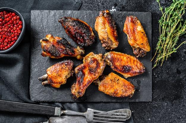 Alitas de pollo picantes y picantes con salsa picante. fondo negro. vista superior.