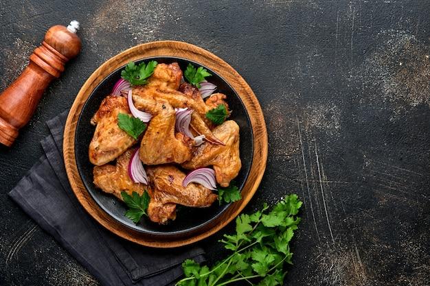 Alitas de pollo a la plancha o barbacoa asada con especias y salsa de tomate en un plato negro. vista superior