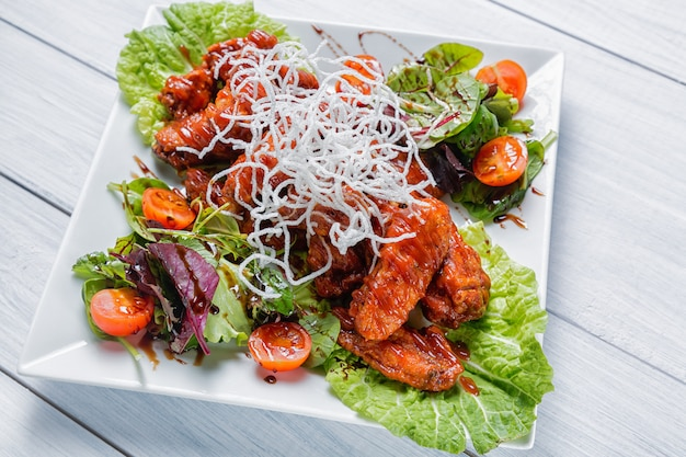 Alitas de pollo con salsa de barbacoa, ensalada, tomates y patatas fritas en un plato blanco